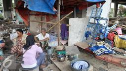 Penghuni kolong Tol beristirahat di tempat tinggalnya sementara usai ditertibkan oleh Pemprov DKI, Jakarta, Jumat (16/9). Sebelumnya, 50 bangunan liar di bawah kolong Tol Sedyatmo, Penjaringan kembali ditertibkan Pemkot Jakut. (Liputan6.com/Yoppy Renato)