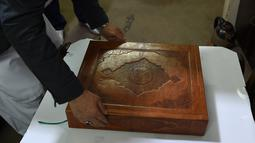 Tampilan Alquran buatan tangan yang dibuat dengan kain sutra di Mourad Khani, Kabul, Afghanistan (19/4). Alquran yang dibuat secara manual ini diharapkan dapat melestarikan tradisi kaligrafi yang telah ada berabad-abad di Afghanistan. (AFP/Wakil Kohsar)