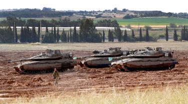 Seorang tentara Israel berjalan melewati tank Merkava yang terparkir di dekat perbatasan dengan Jalur Gaza, Israel, Senin (6/5/2019). Para pemimpin Palestina di Gaza menyetujui gencatan senjata dengan Israel. (JACK GUEZ/AFP)