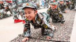 Sejumlah anak-anak berbaris sambil merangkak saat mensimulasikan latihan militer di sebuah taman kanak-kanak di provinsi Henan, China (30/5). (AFP)