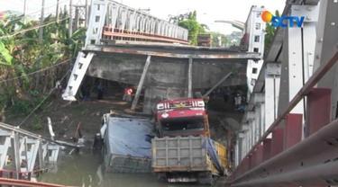 Jembatan Widang, penghubung Lamongan dengan Tuban yang ambruk, kini masih jadi tontonan warga. tiga truk yang ikut terperosok ke Sungai Bengawan Solo, belum dievakuasi.