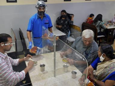 Pramusaji mengenakan pelindung wajah dan masker saat menyajikan makanan kepada pelanggan di restoran yang dibuka kembali usai pelonggaran lockdown di Bangalore, India, Senin (8/6/2020). Untuk keamanan pelanggan, restoran-restoran menyiapkan panel transparan di meja makan. (Manjunath Kiran/AFP)