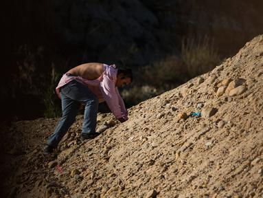 Seorang imigran dengan kemejanya yang  sobek merangkak setelah melintasi pagar kawat berduri dan melompat pagar perbatasan dari Tijuana, Meksiko untuk masuk ke sisi AS ke San Diego, California, (28/12). (AP Photo/Daniel Ochoa de Olza)