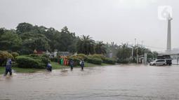 Petugas mengecek genangan air di Jalan Medan Merdeka Barat, Jakarta, Kamis (24/1/2020). Hujan deras yang mengguyur Jakarta sejak pagi tadi mengakibatkan genangan air di Jalan Medan Merdeka Barat. (Liputan6.com/Faizal Fanani)