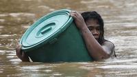 Warga menggunakan wadah plastik sebagai pelampung saat menerobos air banjir di Marikina, Filipina akibat Topan Vamco pada  12 November 2020. Topan Vamco menghantam Filipina dan menyebabkan sungai meluap sehingga membanjiri daerah dataran rendah di timur laut Filipina. (AP Photo/ Aaron Favila)
