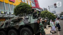 Dua siswa berjalan dekat  Prajurit TNI dan  satu unit kendaraan Anoa di kawasan LTC Glodok, Jakarta, Jumat (18/10/2019). Penjagaan tersebut guna memberikan rasa aman bagi masyarakat menjelang pelantikan presiden dan wakil presiden terpilih, 20 Oktober 2019. (Liputan6.com/Faizal Fanani)