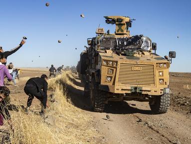 Sejumlah warga Kurdi melemparkan batu ke kendaraan militer Turki di dekat kota Al-Muabbadah, bagian timur laut Hassakah, Suriah (8/11/2019). Pelemparan batu terjadi saat militer Turki melakukan konvoi dengan militer Rusia. (AFP/Delil Souleiman)