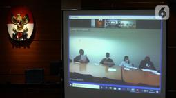 Mantan Komisioner KPU Wahyu Setiawan (kedua kiri) mendengarkan Jaksa Penutut Umum membacakan dakwaan saat sidang secara daring di Gedung KPK, Jakarta, Kamis (28/5/2020). Wahyu menjalani sidang dakwaan terkait kasus dugaan menerima suap pengurusan PAW anggota DPR dari PDIP. (merdeka.com/Dwi Narwoko)