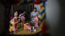 Anggota keluarga Palestina al-Yaqoubi berkumpul di sekitar meja membuat lentera bulan suci Ramadan untuk dijual selama penerapan lockdown di Khan Yunis, di Jalur Gaza, 15 April 2020. Biasanya menjelang Ramadan, warga Palestina berburu lentera tradisional untuk dijadikan dekorasi. (SAID KHATIB / AFP)