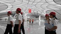Pejabat pabean berkeliling Terminal Bandara Internasional Daxing Beijing, China, Selasa (9/7/2019). Bandara Internasional Daxing Beijing menerapkan desain ruang terbuka. (GREG BAKER/AFP)