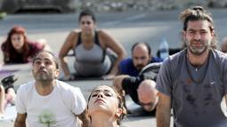 """Seorang wanita melakukan gerakan yoga selama acara """"108 Sun Salutations"""" di ibukota Martir Beirut, Lebanon (22/10). (AFP Photo/Anwar Amro)"""