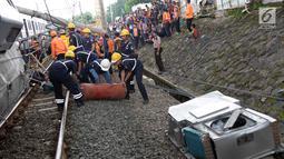 Petugas mengevakuasi rangkaian KRL yang anjlok di perlintasan Kebon Pedes, Bogor, Jawa Barat, Minggu (10/3). KRL tersebut anjlok sekitar pukul 10.15 WIB. (Liputan6.com/Immanuel Antonius)