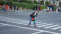 Seorang wanita mengambil foto rekannya dengan latar belakang Jalan MH Thamrin yang masih ditutup oleh aparat keamanan di Jakarta, Jumat (24/5/2019). Ditutupnya Jalan MH Thamrin terkait unjuk rasa menolak hasil Pemilu 2019 dimanfaatkan sebagian warga untuk berfoto. (Liputan6.com/Immanuel Antonius)