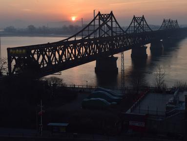 Matahari terbit di belakang Jembatan Persahabatan yang membentang Sungai Yalu antara China dan Korea Utara terlihat dari kota Dandong di provinsi Liaoning timur laut China (22/2). (AFP Photo/Greg Baker)