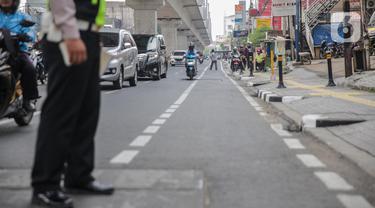 Petugas satlantas mensterilkan jalur sepeda di kawasan Blok A, Jakarta, Senin (25/11/2019). Mulai hari ini, polisi akan menilang para pengendara kendaraan bermotor yang nekat masuk dan melintas di jalur sepeda. (Liputan6.com/Faizal Fanani)