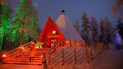 Pengunjung memasuki sebuah restoran di Desa Sinterklas atau Santa Claus Village, di Lingkar Arktik, Finlandia, 15 Desember 2016. Kawasan yang tertutup salju pada musim dingin ini makin menguatkan suasana 'White Christmas'. (REUTERS/Pawel Kopczynski)