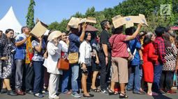 Warga mengantre di kawasan Silang Monas, untuk mengikuti Open House Jokowi di Istana Kepresidenan, Jakarta Rabu (5/6/2019). Meski tempatnya terbatas, Presiden Jokowi menggelar Open House yang dibagi dua sesi bagi pejabat negara dan masyarakat. (Liputan6.com/HO/Grandy)