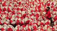 Pekerja mengemas paket bantuan sosial (bansos) di Gudang Food Station Cipinang, Jakarta, Rabu (22/4/2020). Pemerintah pusat menyalurkan paket bansos selama tiga bulan untuk mencegah warga mudik dan meningkatkan daya beli selama masa pandemi COVID-19. (Liputan6.com/Johan Tallo)