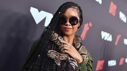 H.E.R. berpose saat menghadiri MTV VMA's 2019 di New Jersey, AS (26/8/2019).  H.E.R. tampil membawa ular di lehernya sebagai aksesoris dan mendapatkan pujian dari netizen. (Photo by Charles Sykes/Invision/AP)