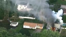 Gambar dari rekaman video  menunjukkan kobaran api dan kepulan asap kebakaran rumah di Lawrance, dekat Boston, AS, Kamis (13/9). Rentetan ledakan dan kebakaran di tiga komunitas utara Boston tersebut menyebabkan beberapa warga terluka. (WCVB via AP)