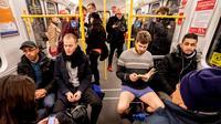 Seorang pria tanpa mengenakan celana membaca buku selama No Pants Subway Ride di sebuah kereta bawah tanah di Berlin, Jerman (13/1). Acara ini dimulai pada tahun 2002 dengan peserta hanya tujuh orang. (AFP Photo/Christoph Soeder)