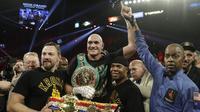 Petinju Inggris Tyson Fury merayakan kemenangannya atas petinju AS Deontay Wilder pada pertandingan tinju kelas berat WBC di Las Vegas (23/2/2020). Tyson Fury berhasil memenangkan pertarungan di ronde ketujuh. (AP Photo/Isaac Brekken)