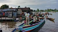 Wisatawan asing sedang menikmati berinteraksi dengan pedagang di Pasar Terapung Lok Baintan, Banjarmasin (Liputan6.com/Pool/Kadek Arini)