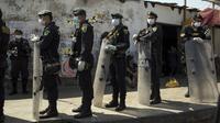 Polisi berjaga di luar Penjara Lurigancho saat protes narapidana di Lima, Peru, Selasa (28/4/2020). Narapidana mengeluhkan pihak berwenang tidak berbuat cukup untuk mencegah penyebaran COVID-19 dalam penjara. (AP Photo/Rodrigo Abd)