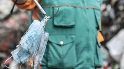 Potret Ikhsanudin menunjukkan masker di Dipo Sampah Kecamatan Pademangan, Ancol, Jakarta, Rabu (24/2/2021). Rata-rata tim di Dipo Ancol mampu mengumpulkan limbah masker bekas pemakaian warga mencapai setengah hingga 1 kilogram, tergantung volume sampah. (merdeka.com/Iqbal S. Nugroho)