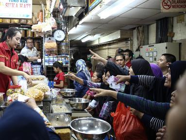 Sejumlah calon pembeli mengantre membeli kue kering di Pasar Jatinegara, Jakarta, Senin (27/6). Meskipun Hari Raya Idul Fitri atau Lebaran masih sepekan lagi, namun toko kue kering di Pasar Jatinegara mulai diserbu pembeli. (Liputan6.com/Faizal Fanani)