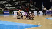 Atlet basket kursi roda Jepang, Rie Odajima (kiri), membantu atlet Afghanistan, Farzana Mohammadi, pada pertandingan Asian Para Games 2018 di Hall Basket Senayan, Senin (8/10/2018). (Asian Para Games 2018)