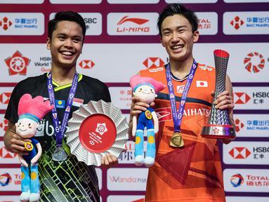 Tunggal putra Indonesia, Anthony Ginting, naik podium bersama tunggal Jepang, Kento Momota, pada BWF World Tour 2019 di Tianhe Gymnasium, Guangzhou, Minggu (15/12). Ginting kalah 21-17, 17-21 dan 14-21 dari Momota. (AFP/STR)
