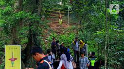 Pengunjung wisata Kebun Raya Bogor saat melihat Bunga Bangkai yang sedang mekar di Kebun Raya Bogor, Minggu (5/1/2020). Hari terakhir liburan sekolah, Kebun Raya Bogor menjadi tujuan wisata favorit bagi warga.  (Merdeka.com/Fotografer Magang: Muhammad Fayyadh)