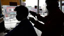 Tukang cukur mengenakan alat pelindung diri (APD) saat memotong rambut pelanggan di sebuah tempat pangkas rambut di Manila, 8 Juni 2020. Filipina mengizinkan barbershop dan salon kecantikan beroperasi kembali dengan menerapkan langkah-langkah ketat pencegahan pandemi Covid-19. (AP/Aaron Favila)