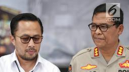 Wadir Reskrimum Polda Metro Jaya AKBP Ade Ary Syam Indradi (kiri) menunjukkan foto tersangka pengancam pemenggalan terhadap Presiden Joko Widodo atau Jokowi di Mainhall PMJ, Jakarta, Senin (13/5/2019). Tersangka ditangkap di rumah kerabatnya di kawasan Parung, Bogor. (Liputan6.com/Faizal Fanani)