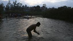 Seorang pria Nepal mandi air suci di sungai Bagmati selama festival Kuse Aunsi di Kathmandu (30/8/2019). Kuse Aunsi sebagai bentuk penghormatan kepada ayah bimbingan dan ajarannya dalam kehidupan. (AP Photo/Niranjan Shrestha)