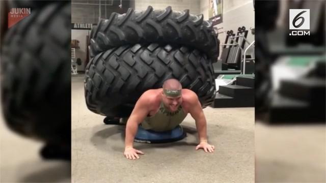 Seorang pria terekam melakukan push-up dengan memikul ebuah ban raksasa di punggungnya.