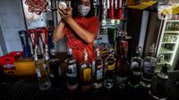 Pekerja menyiapkan minuman keras atau miras di mesin pendingin di salah satu kafe kawasan Jakarta Selatan, Selasa (2/3/2021). Aturan yang diteken oleh Presiden Joko Widodo pada 2 Februari 2021 terkait memperbolehkan masyarakat untuk berinvestasi di produk miras dicabut. (Liputan6.com/Johan Tallo)