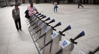 Warga melihat instalasi seni berbentuk senjata api dari Program Chicago Gun Share di Daley Center Plaza, Chicago, Illinois (14/5). Seni instalasi ini dipajang untuk mencegah kekerasan dari penggunaan senjata api. (Scott Olson / Getty Images / AFP)