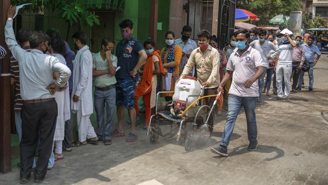 Petugas kesehatan membawa mesin sanitasi di kursi roda sambil membersihkan kompleks rumah sakit ketika orang-orang menunggu untuk tes COVID-19 di Noida, pinggiran New Delhi, India, Rabu (7/4/2021). India mencapai puncak baru dengan 115.736 kasus COVID-19 dalam 24 jam. (AP Photo/Altaf Qadri)