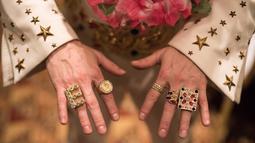 Kontestan menunjukkan cincinnya saat mengikuti Kejuaraan Elvis Eropa di Hilton Metropole Hotel di Birmingham, Inggris (5/1). Acara ini diikuti 80 peserta yang berkompetisi untuk meraih gelar juara Eropa mirip Elvis Presley. (AFP Photo/Oli Scarff)