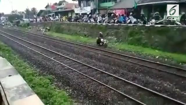 Seorang pemotor di Cimindi, Bandung nekat lintasi rel kereta api demi hindari macet. Beruntung tak ada kereta yang lewat saat kejadian.