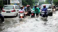 Pengendara sepeda motor mendorong motornya yang mogok setelah menerobos banjir di kawasan Kemang, Jakarta, Selasa (4/10). Hujan deras yang mengguyur Jakarta kembali menyebabkan kawasan Kemang tergenang air hingga 40 cm. (Liputan6.com/Gempur M Surya)