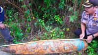 Kapolsek Tenayan Raya Pekanbaru Kompol Hanafi mengukur benda yang diduga bom di lokasi penggalian pipa. (Liputan6.com/M Syukur)