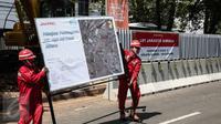 Pekerja membawa spanduk proyek Light Rail Transit (LRT) Velodrome di kawasan Rawamangun, Jakarta, Rabu (22/6).Prioritas pembangunan dengan rute Kelapa Gading-Veledrome-Rawamangun. (Liputan6.com/Faizal Fanani)
