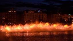 Petugas pemadam kebakaran menyemprotkan air ke Sungai Vltava berhias cahaya kuning untuk menandai HUT ke-100 Ceko di Praha, Sabtu (2/6). (Michal Cizek/AFP)