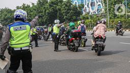 Petugas kepolisian lalu lintas memberhentikan pengendara motor saat Operasi Zebra Jaya 2020 di kawasan Cawang, Jakarta, Senin (26/10/2020). Operasi Zebra Jaya dilaksanakan pada 26 Oktober-8 November 2020 untuk menekan jumlah pelanggaran lalu lintas. (Liputan6.com/Faizal Fanani)