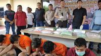 Tersangka narkoba jenis pil ekstasi dan sabu dihadirkan bersama barang bukti haramnya di Polresta Pekanbaru. (Liputan6.com/M Syukur)