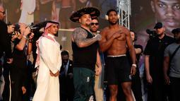 Petinju kelas berat Anthony Joshua (kanan) dan Andy Ruiz Jr (kiri) berpose saat timbang badan resmi di Riyadh, Arab Saudi, Jumat (6/12/2019). Anthony Joshua akan menghadapi Andy Ruiz Jr pada 7 Desember 2019. (AP Photo/Hassan Ammar)