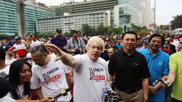 Walikota London, Boris Johnson (tengah) berbincang dengan Gubernur DKI Jakarta, Basuki Tjahaja Purnama (berkaos hitam) di kawasan Bundaran HI Jakarta, Minggu (30/11/2014). (Liputan6.com/Faizal Fanani)